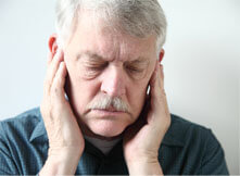 Older man in pain holding his ears